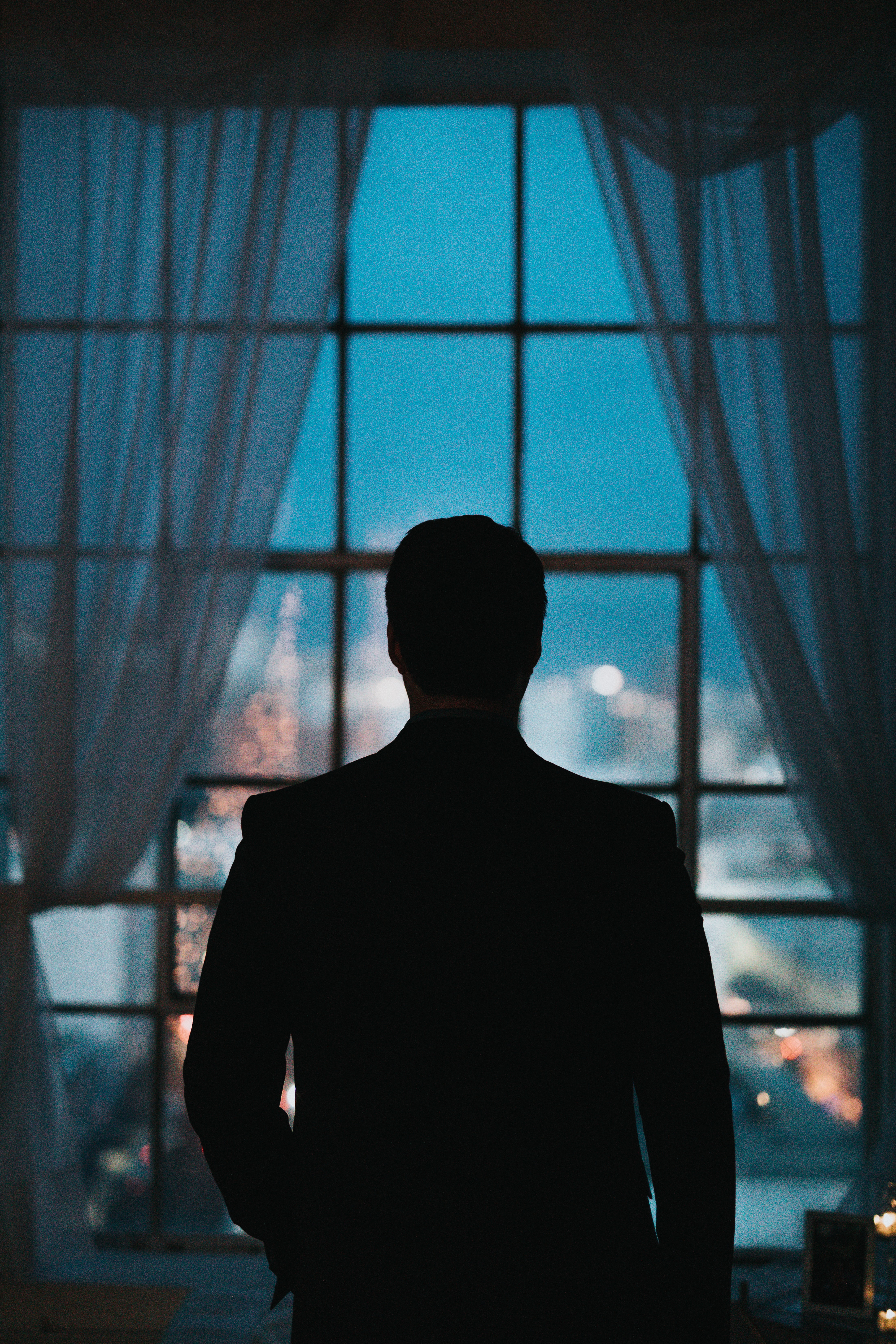 silhouette of person standing against windowpane