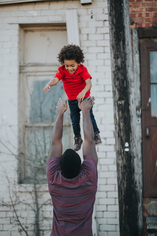 man wearing purple and red shirt catching child wearing red shirt