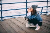woman sitting on brown boardwalk holding DSLR camera taking photo