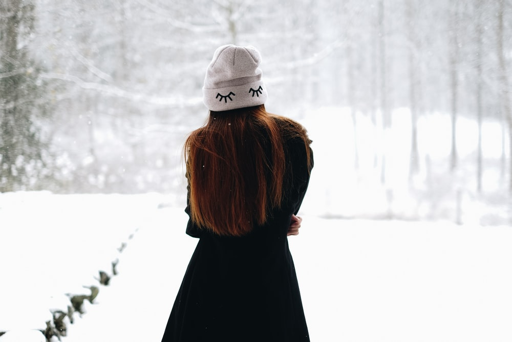 woman standing on white snow-covered field