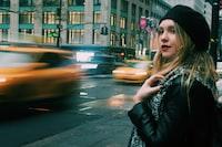 woman wearing black leather jacket standing on street