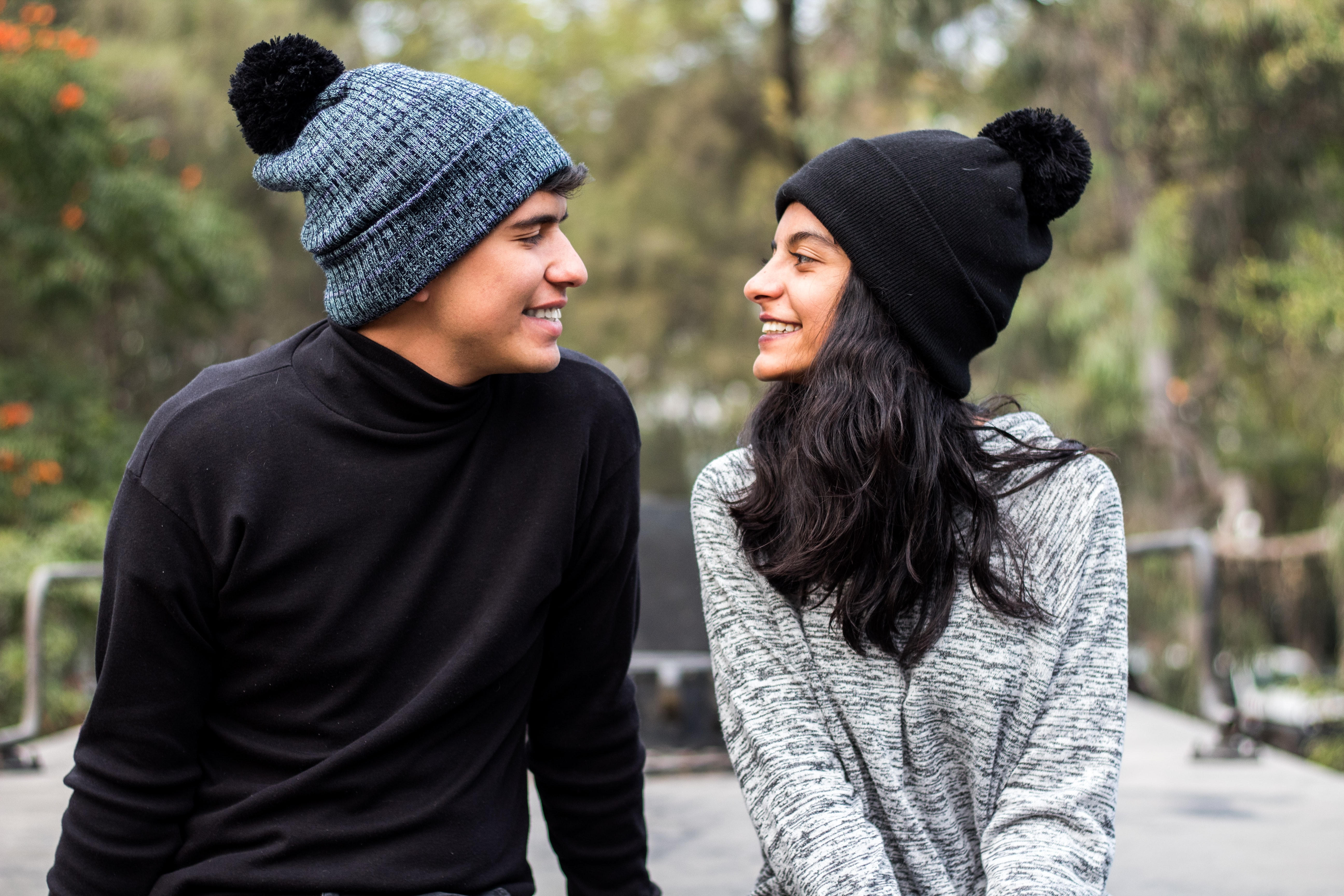 smiling woman sitting in front of the man wearing blue knit cap