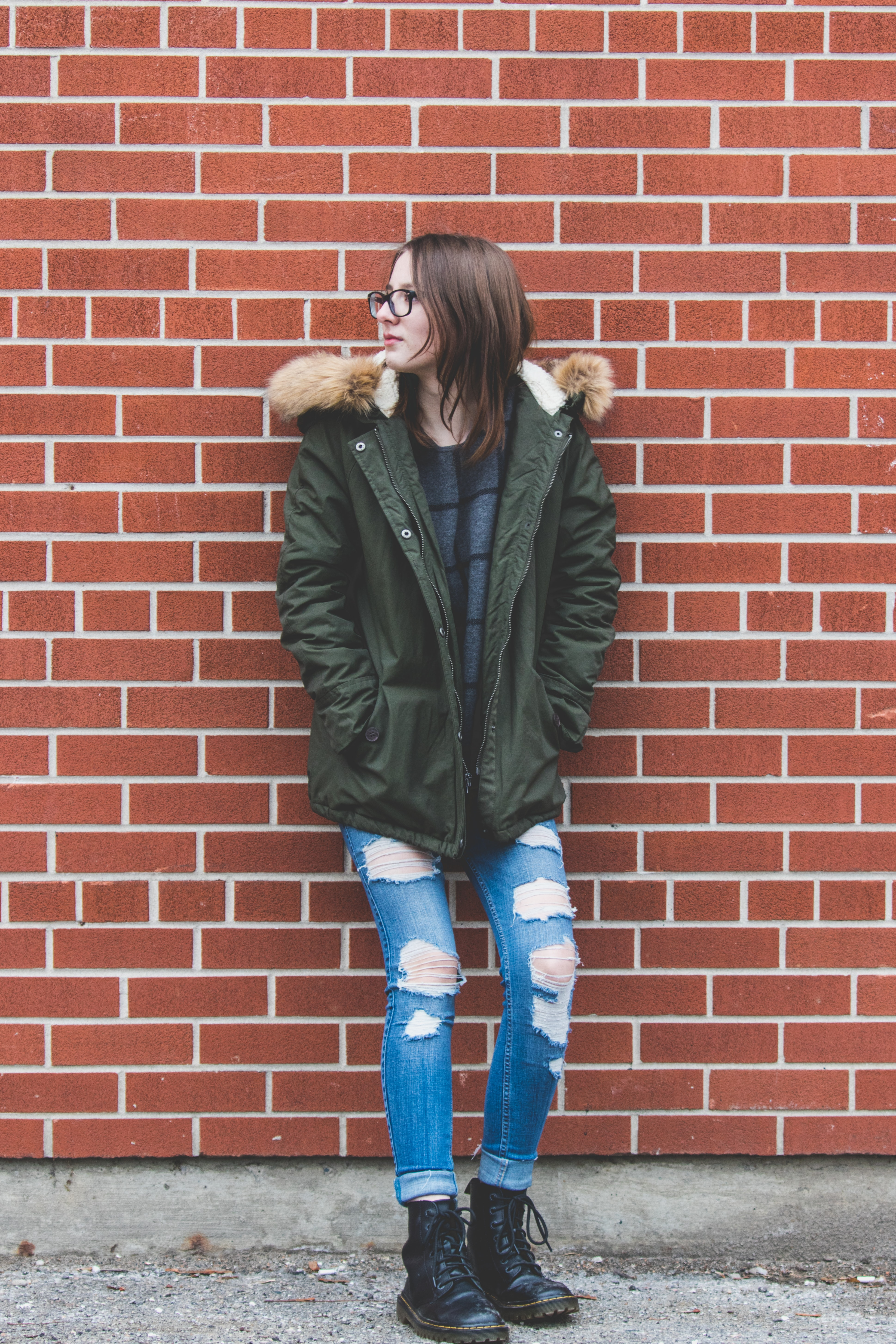 woman in green parka, boyfriend jeans, and black boots leaning on brick wall