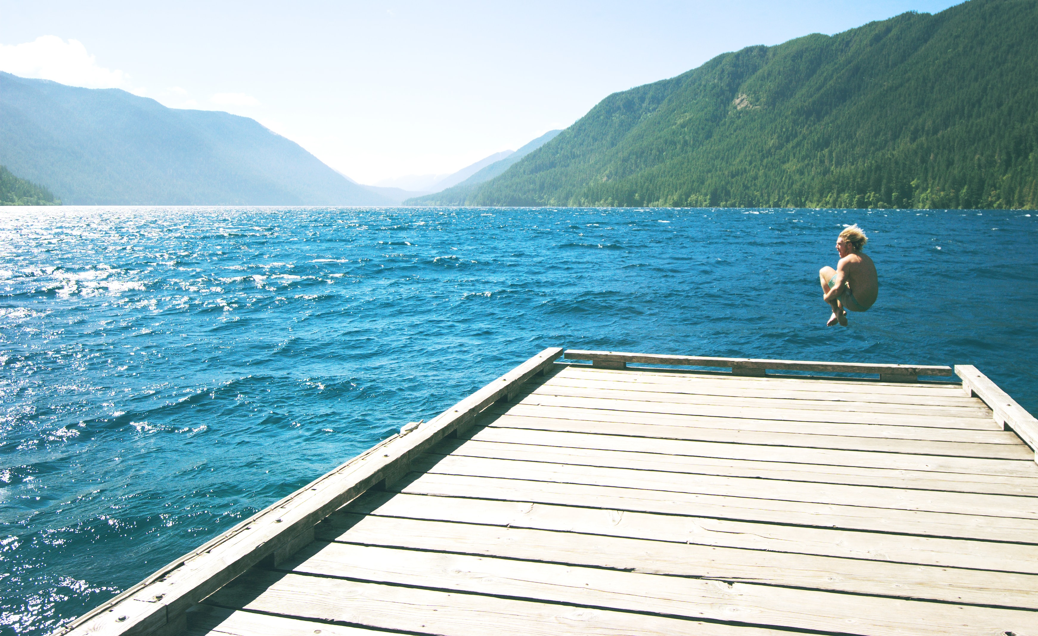 topless person jumping towards water from white wooden dock
