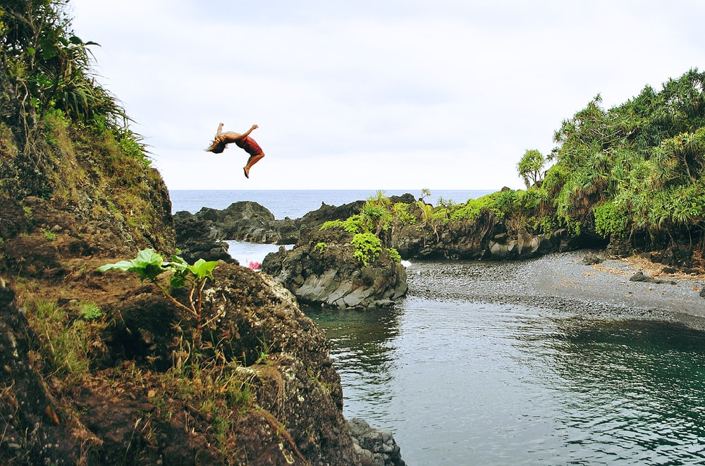 man back tumbling on gray rock formation near sea during daytime