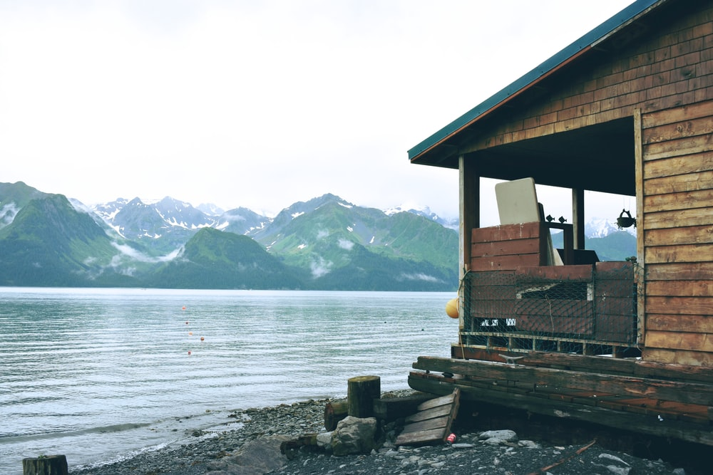 brown wooden cabin at shore with view of green mountain range across body of water during daytime