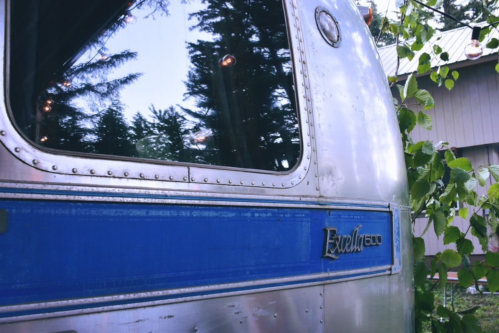 photography of gray and blue Air Stream Excella 1500 trailer