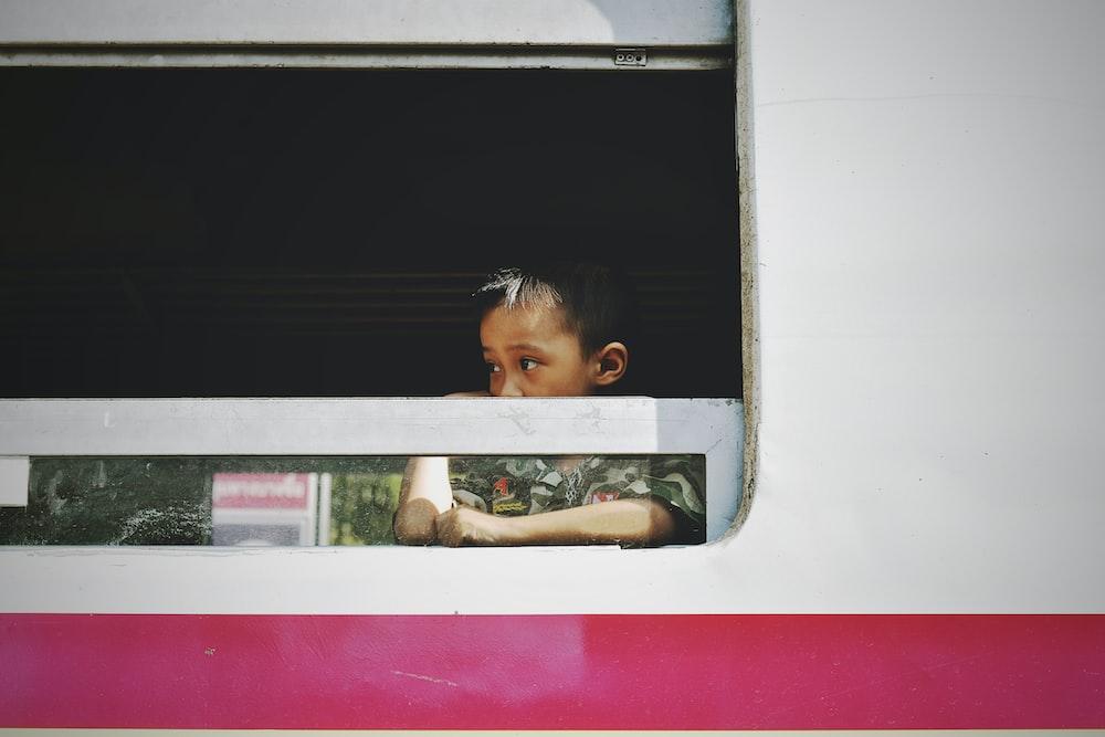 boy near vehicle window during daytime photography