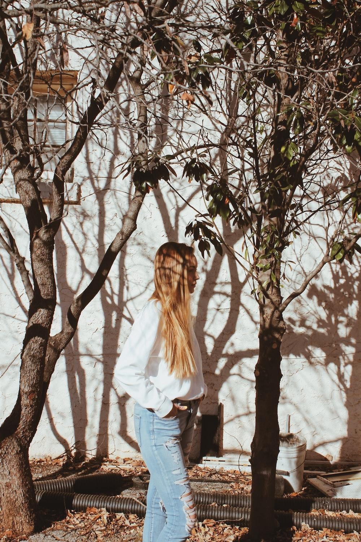 woman standing beside bare tree