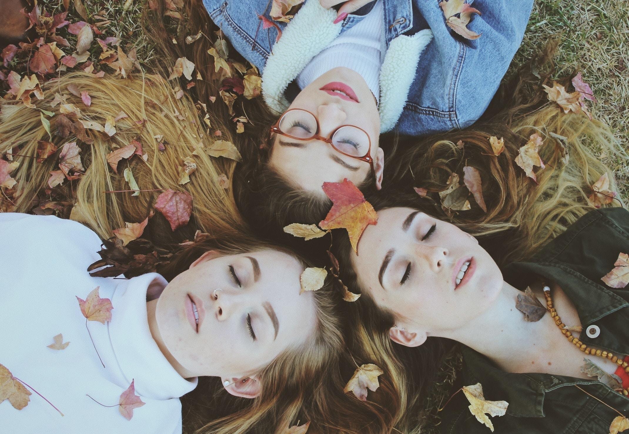 three women laying on green grass