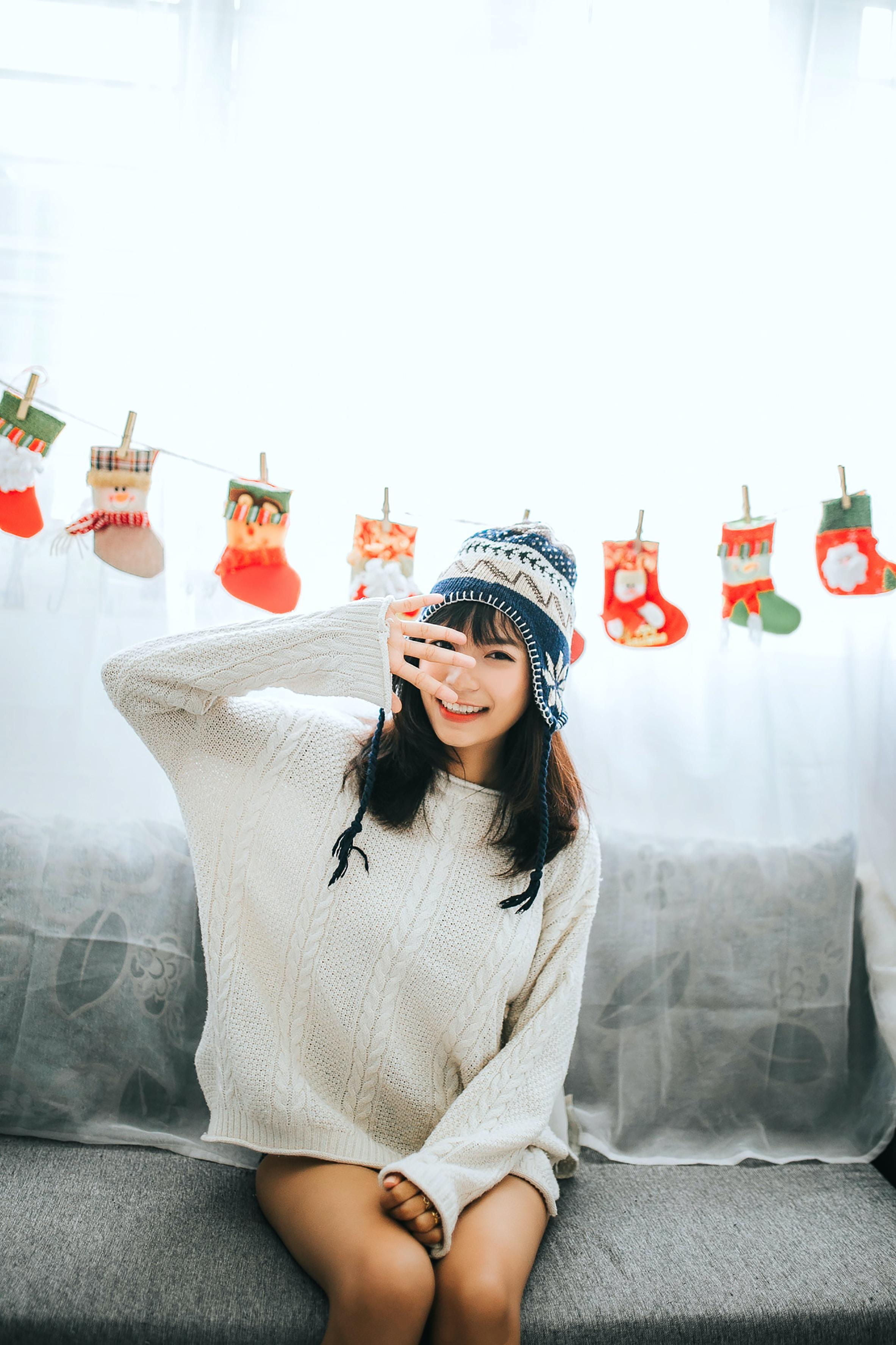 woman wearing white sweater sits on gray fabric sofa