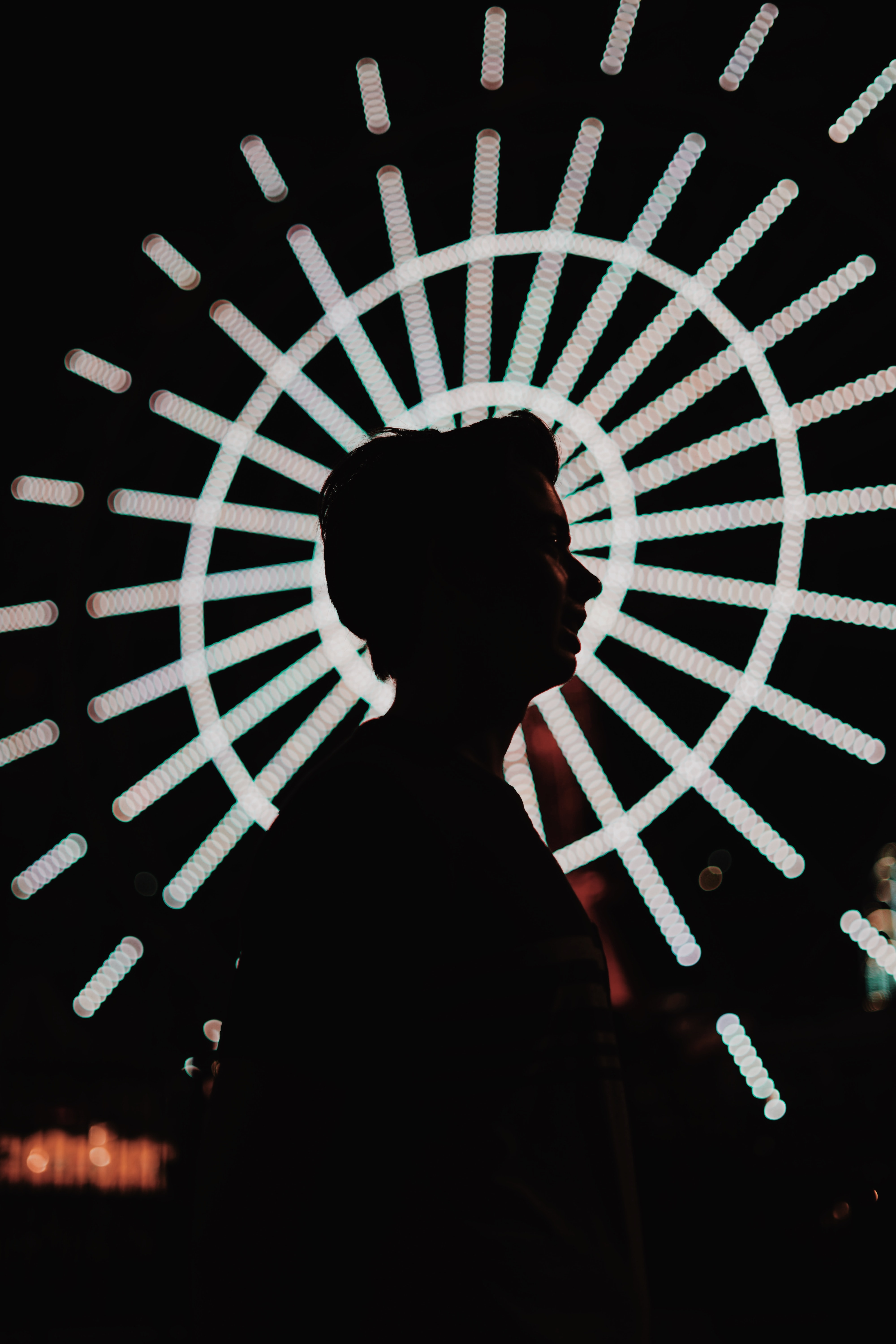 silhouette photography of woman standing near lighted ferris wheel