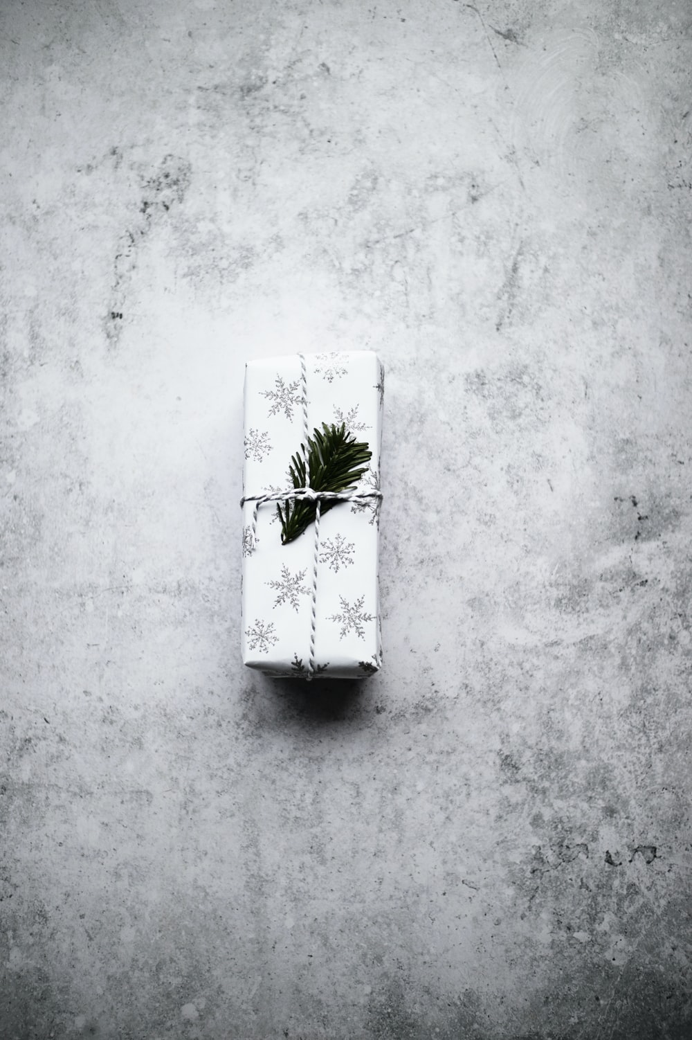 white and black snowflake print gift box on gray surface