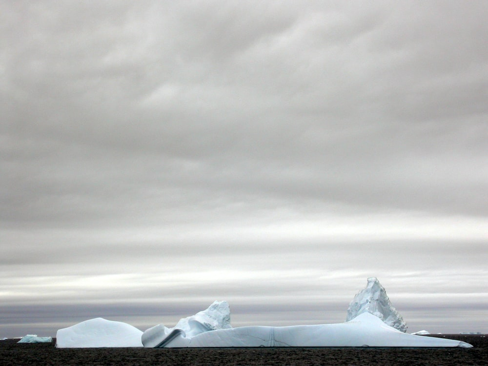 ice berg surrounded by body of water under dark cloudy sky