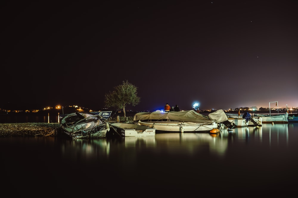 white boats parked on shore during nighttime