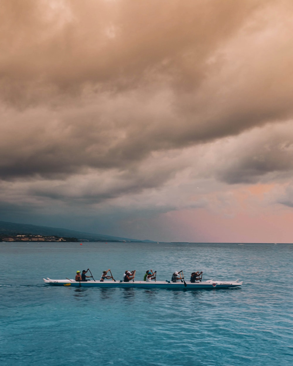 people on white and blue boat paddling under gray clouds during daytime