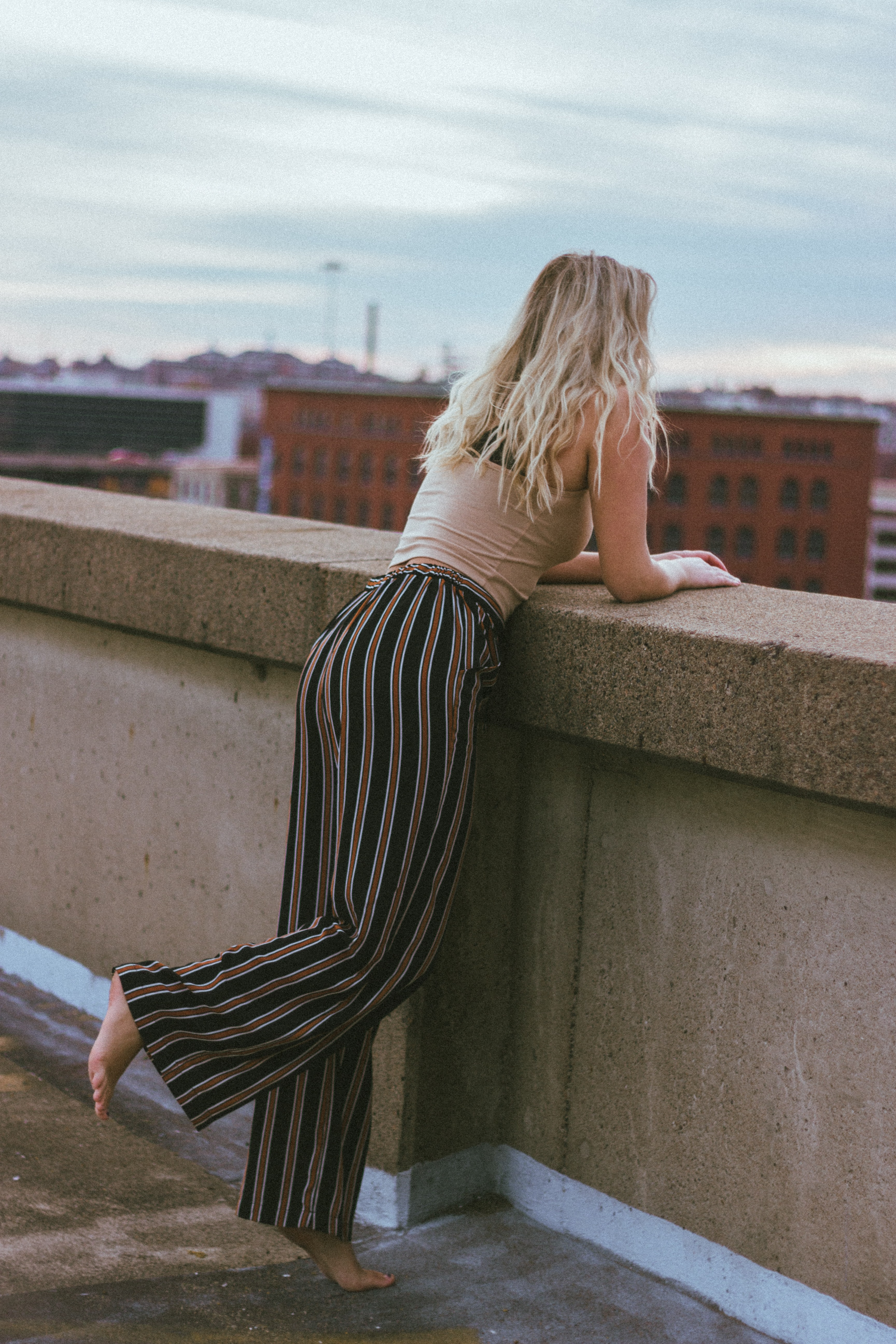 woman leaning on concrete wall