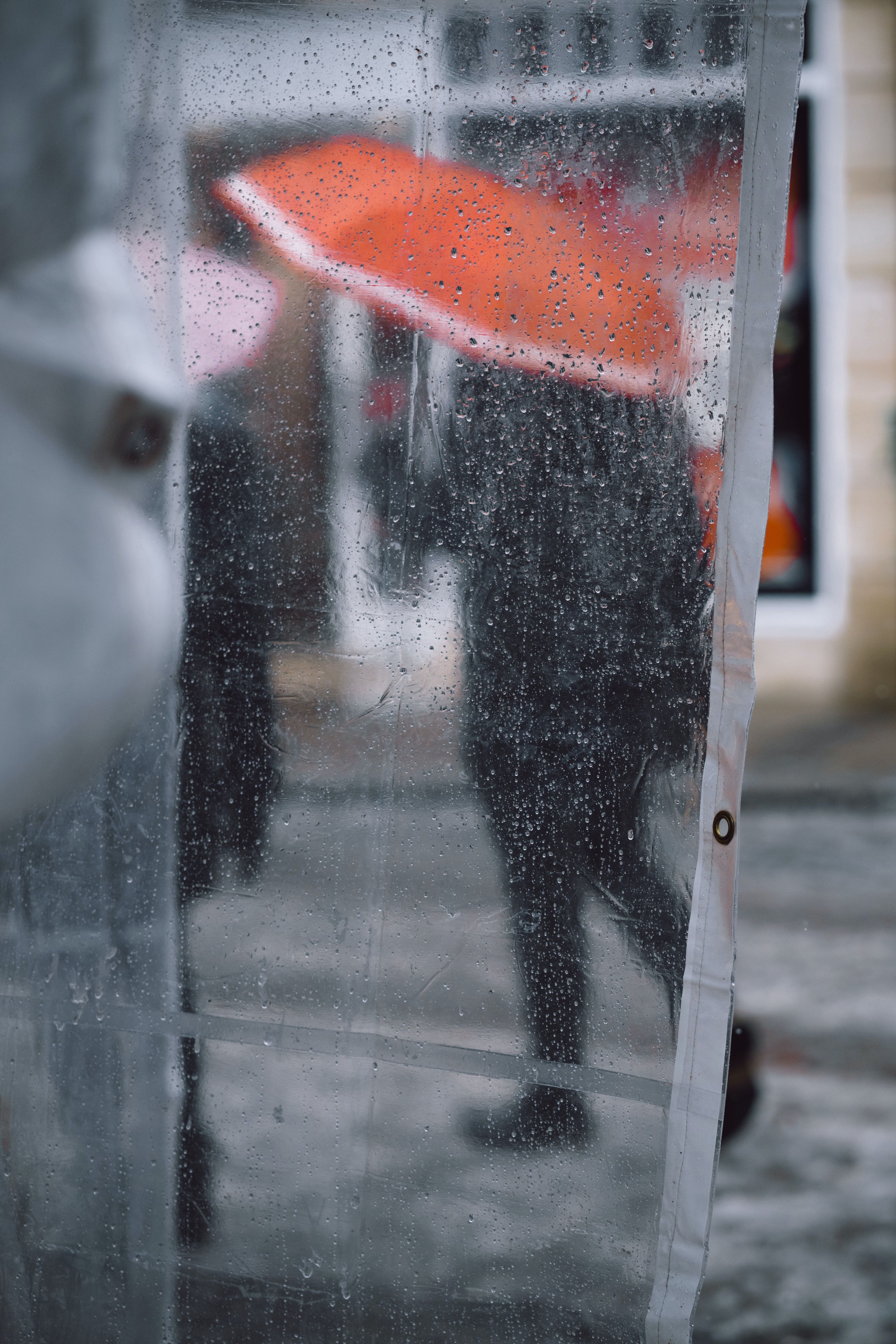 clear plastic coat with water drops showing people using umbrella