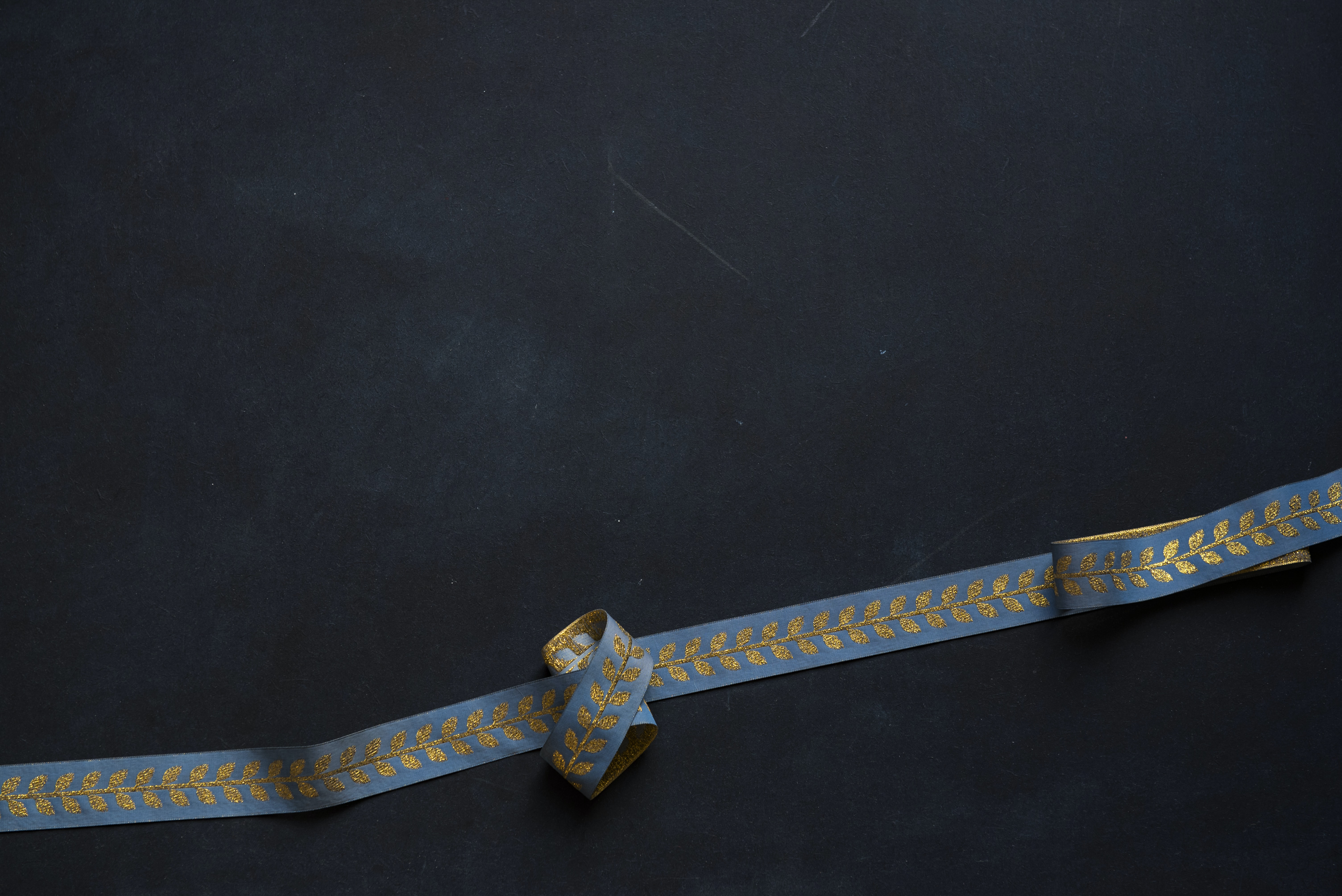 blue and beige floral strap on black surface