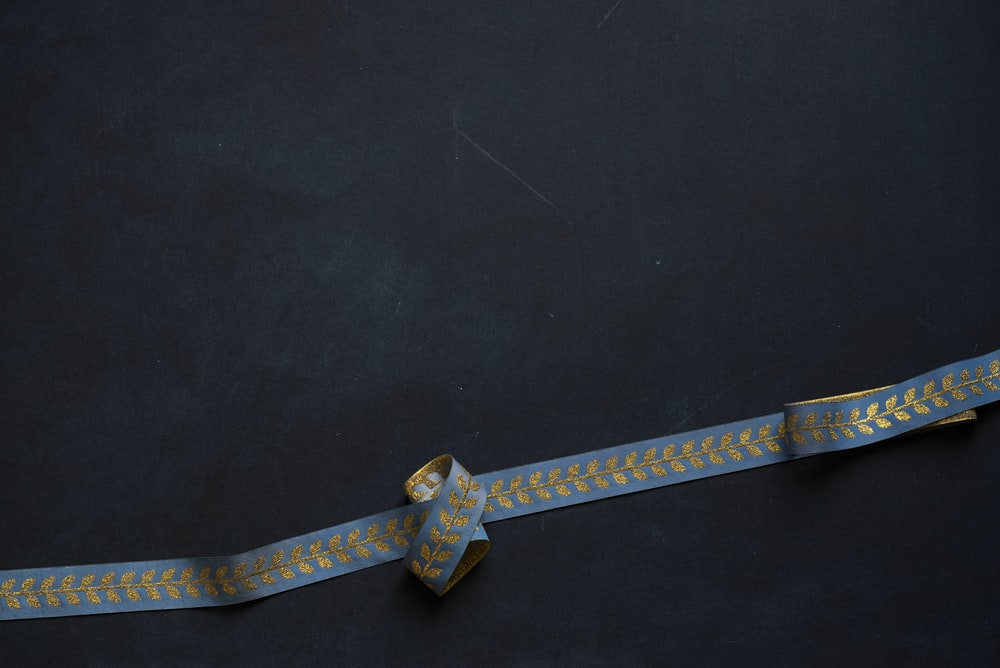 blue and beige floral strap on black surface