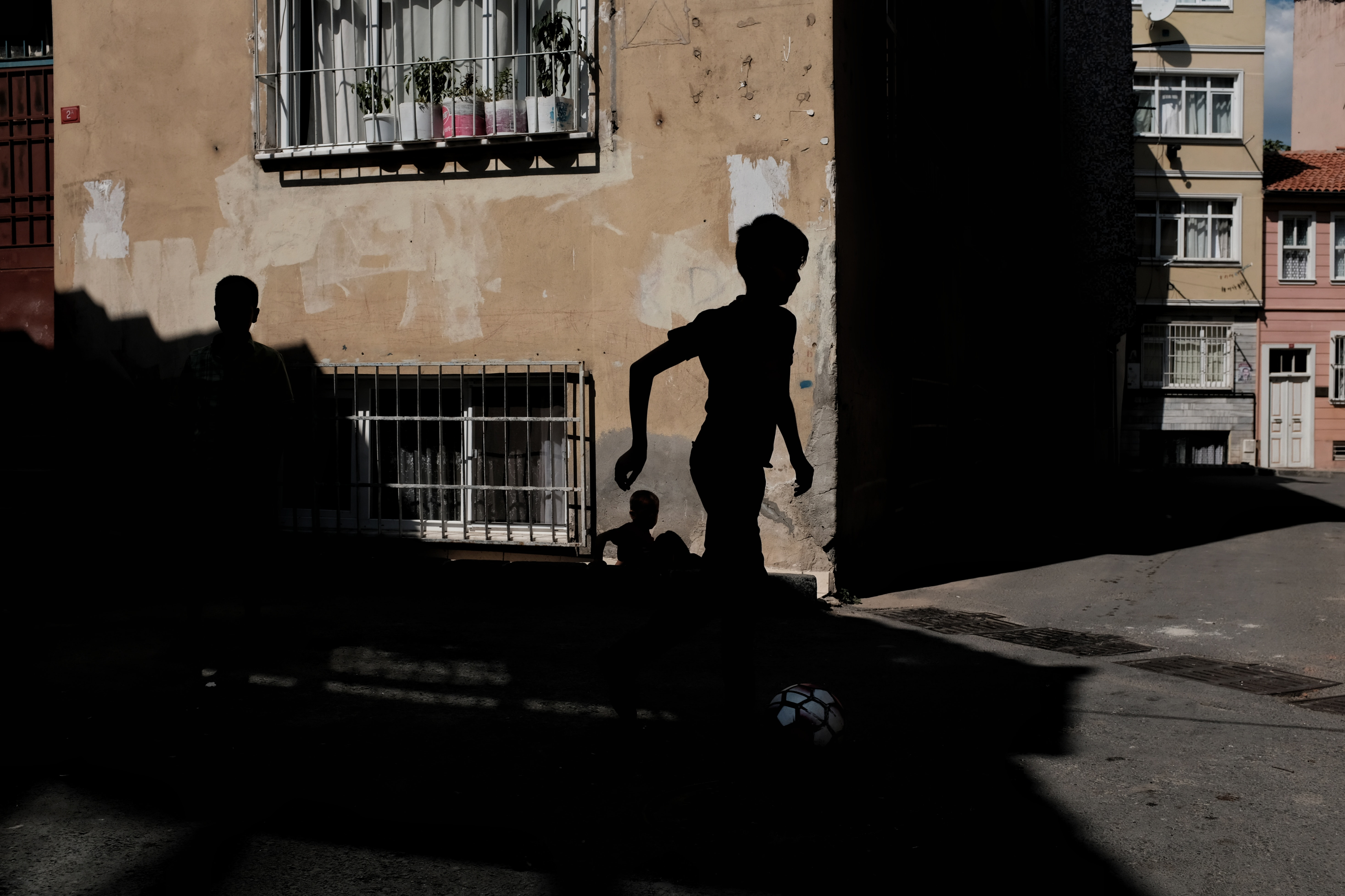 silhouette of boy running near brown concrete building during daytime