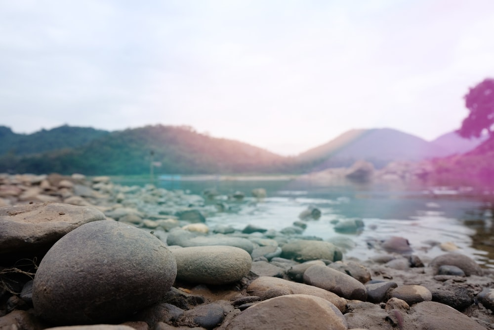 photo of body of water surrounded with rocks and mountain range