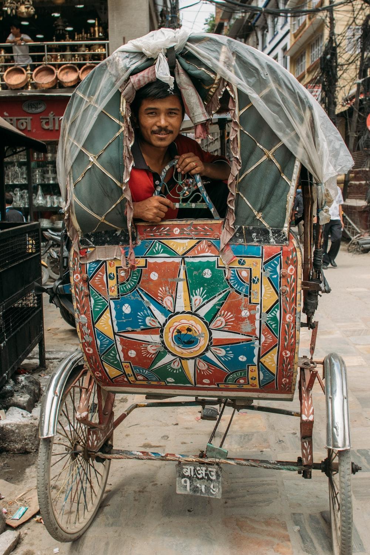 man in red shirt riding brown and green rickshaw