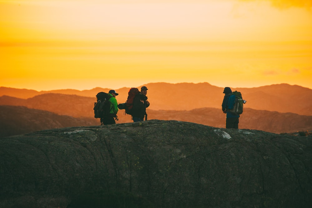 three hikers standing on cliff during golden time
