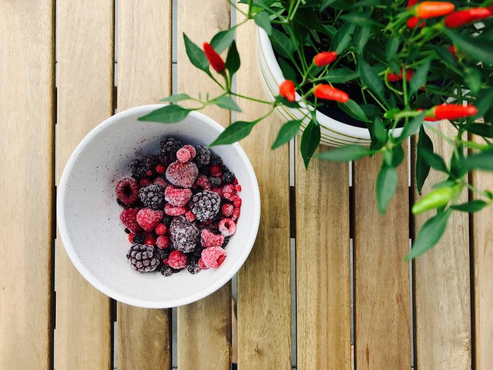 raspberries and black berries in white ceramic bowl