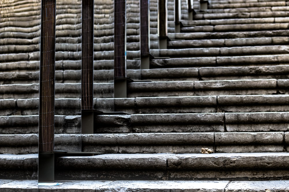 gray concrete stairs with pillars at daytime