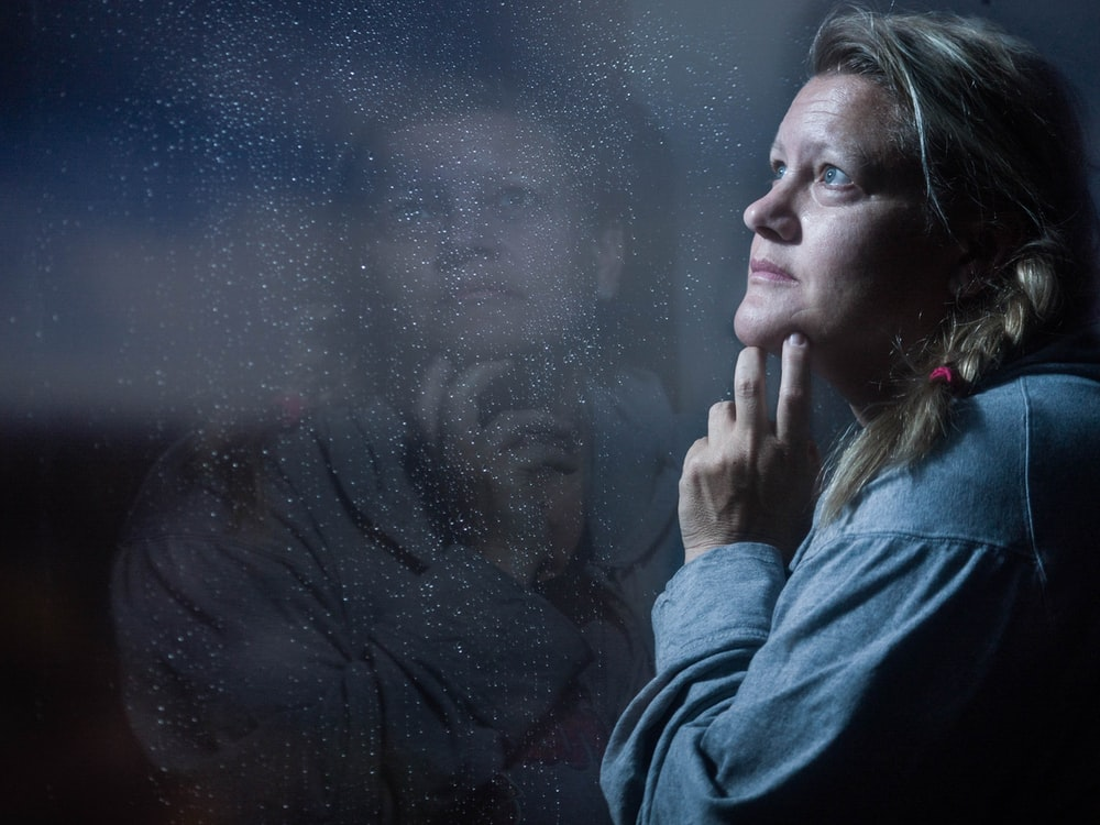 clear glass window panel casting reflection of woman touching her jaw
