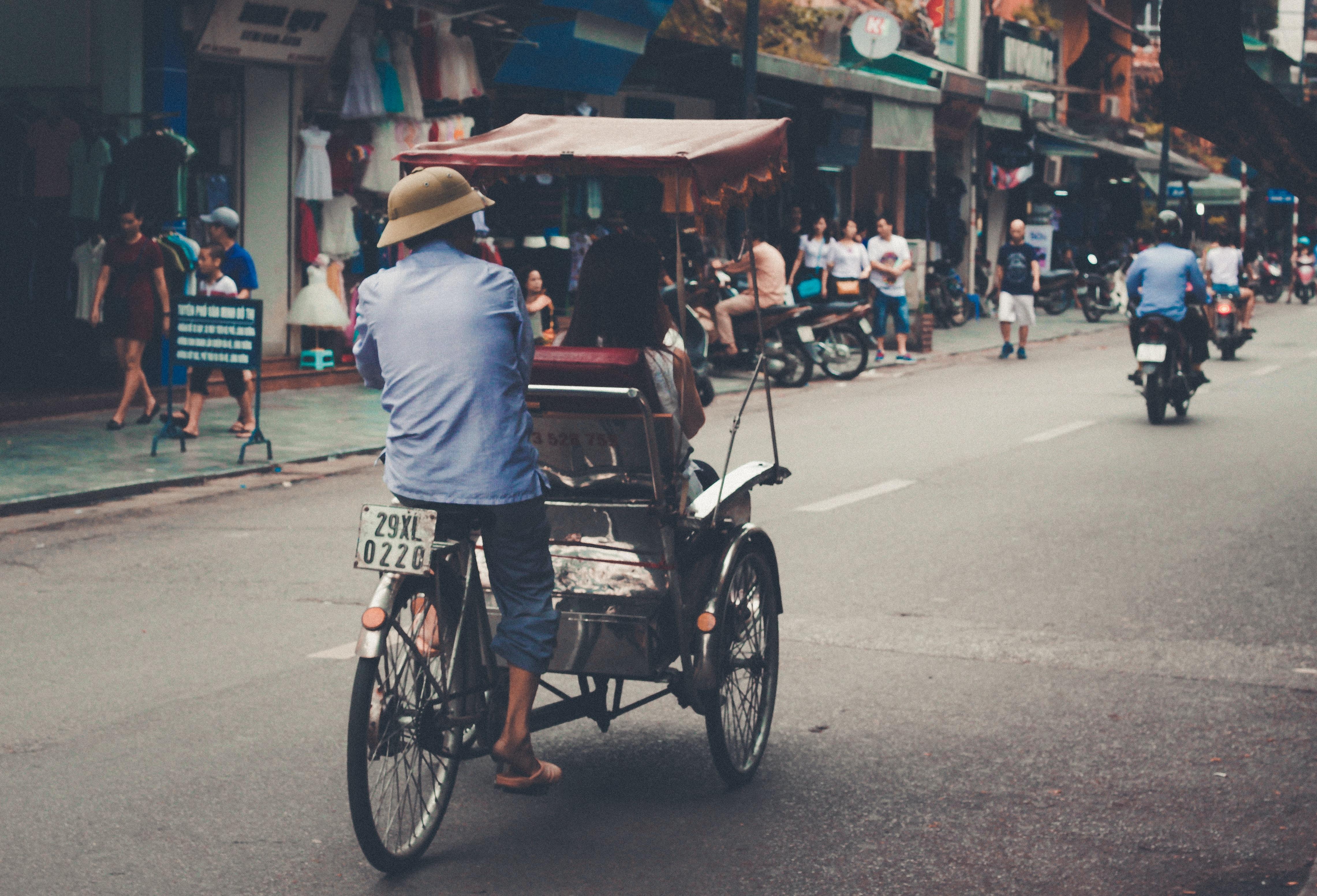 man wearing blue top riding on bicycle