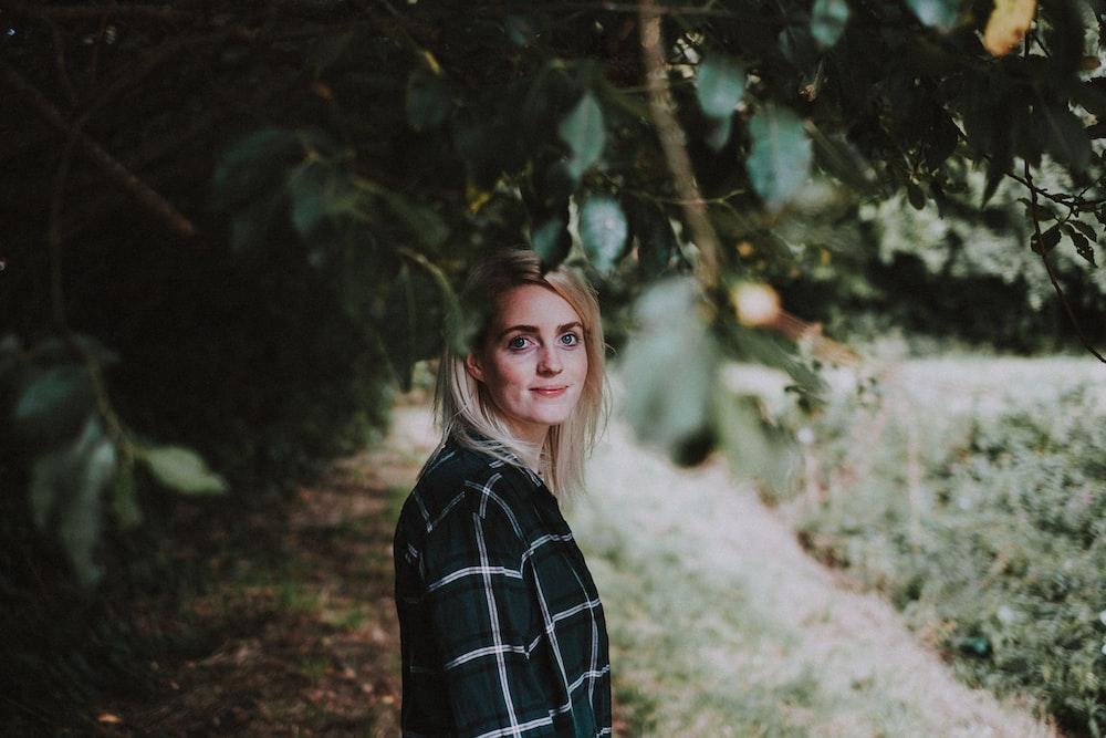 woman wearing black top standing under tree