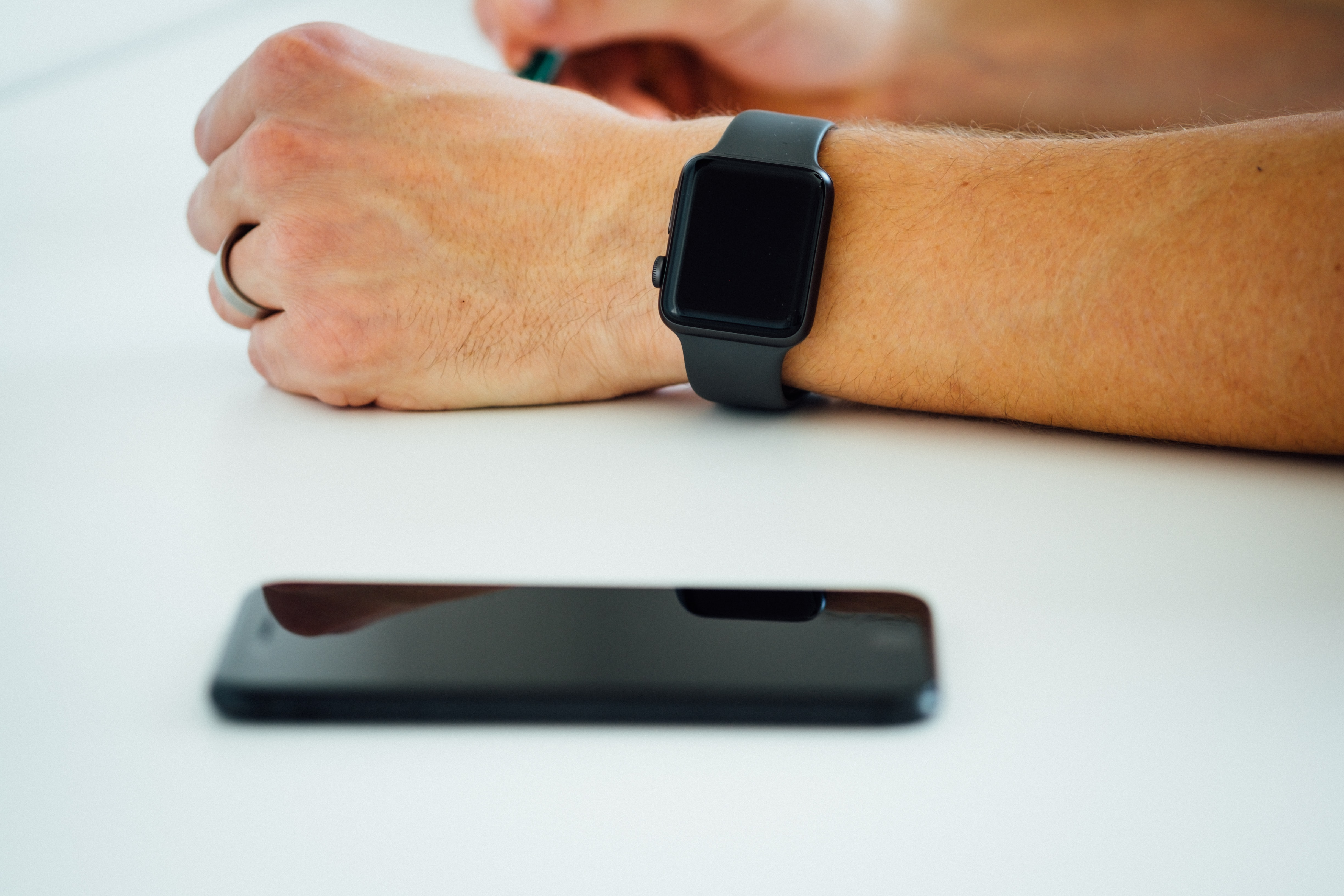 black smartphone near person's hand wearing black smartwatch