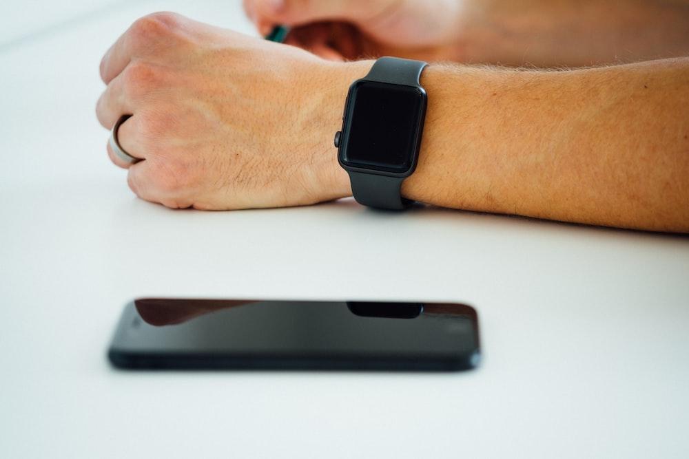 black smartphone near person's hand wearing black smartwatch