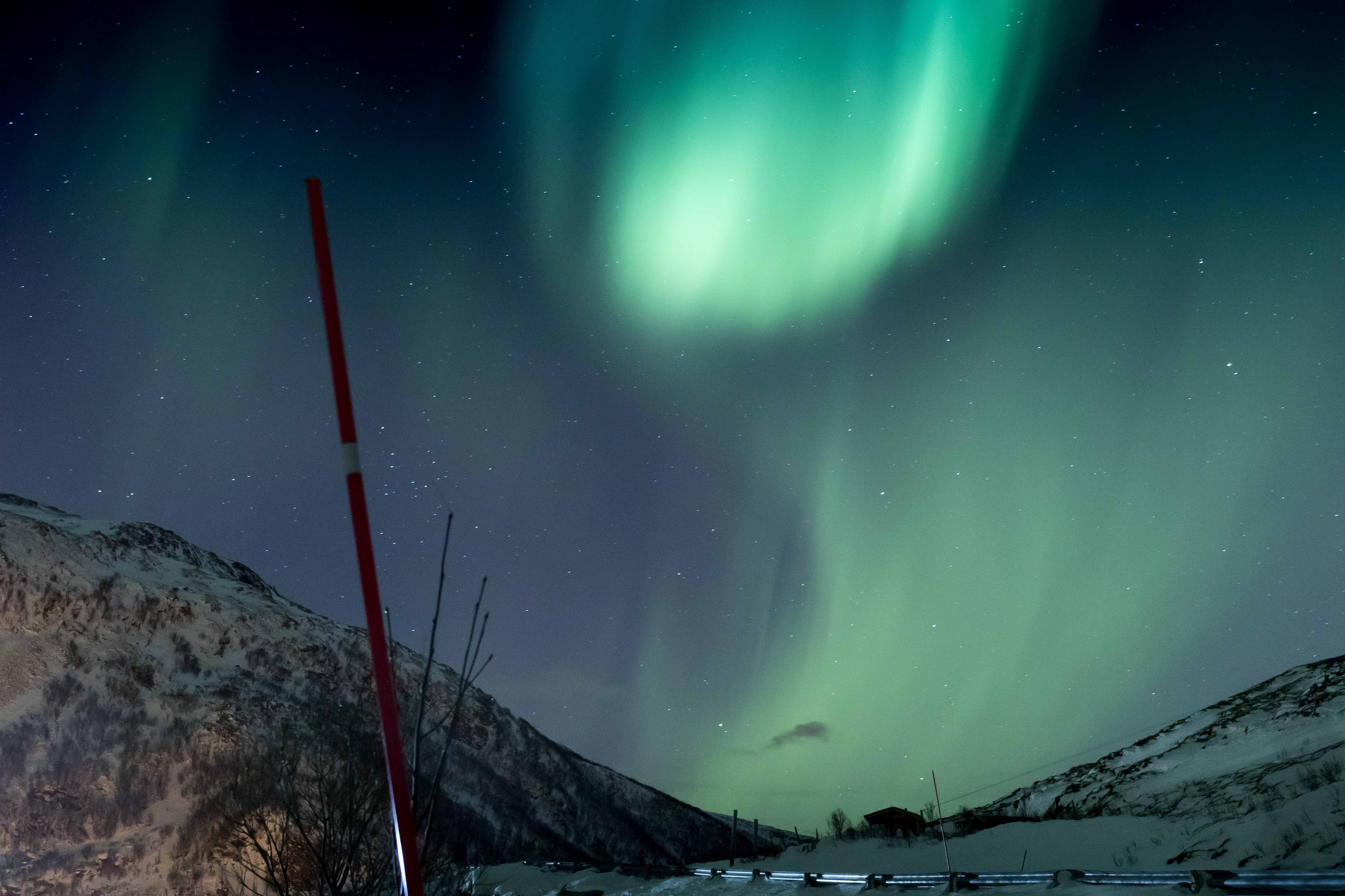 Aurora Borealis about mountain range covered with snow during nighttime