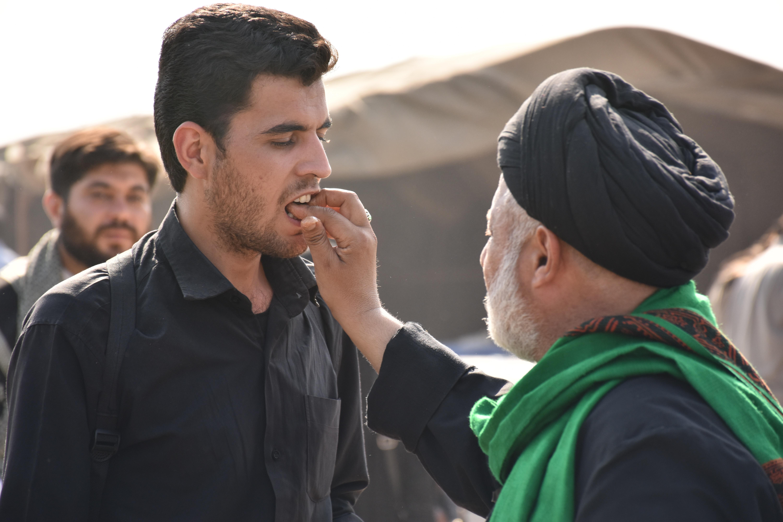 man wearing green scarf touching the mouth of man in black dress shirt