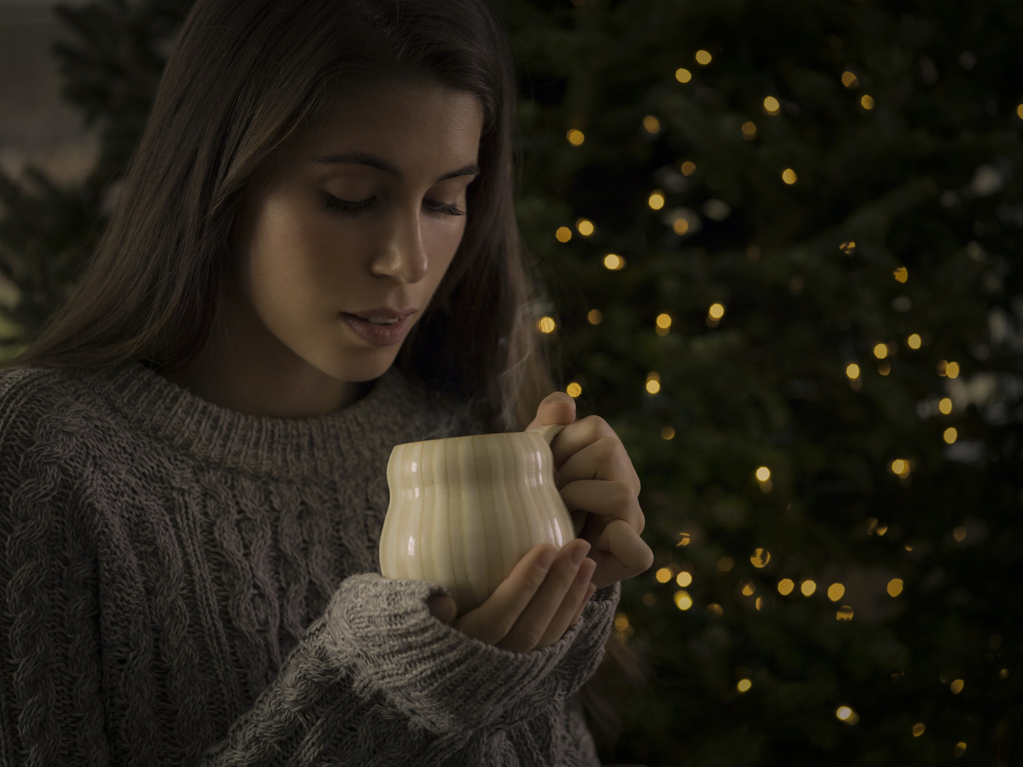 man holding white ceramic mug standing in front of lighted green Christmas tree