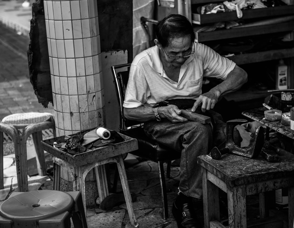 grayscale photo of man cleaning shoes