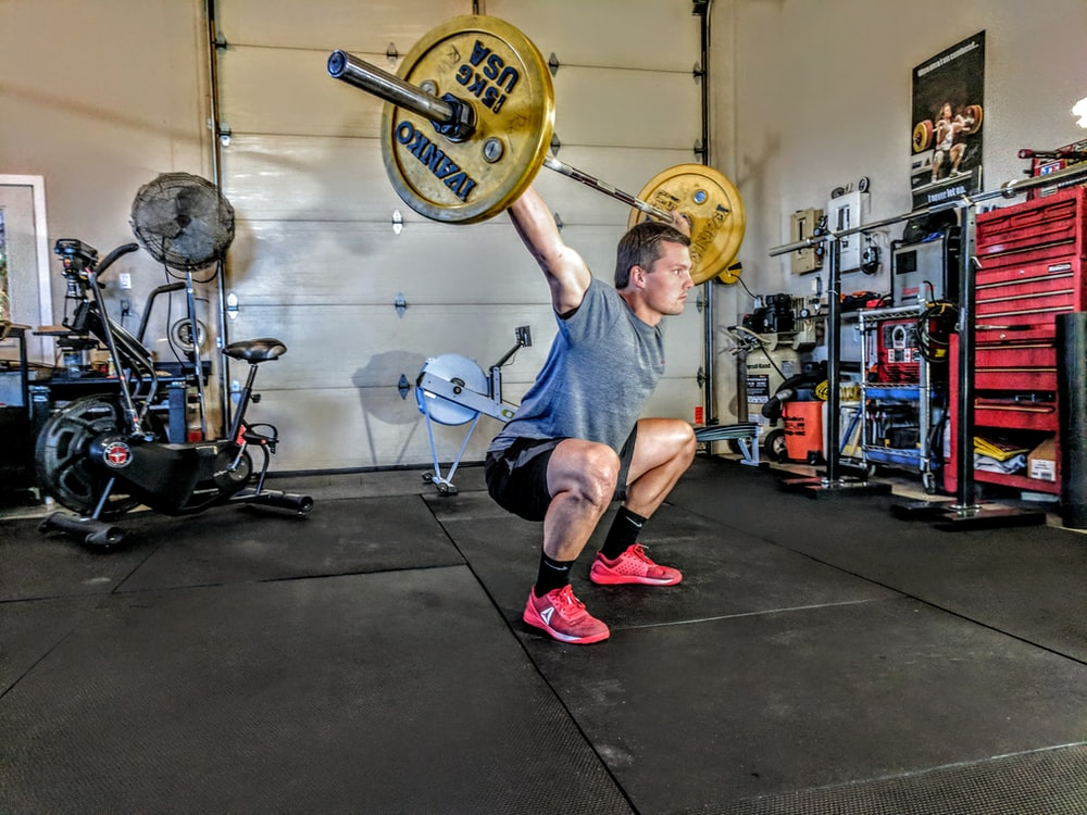 man in gray t-shirt lifting gray and yellow barbell