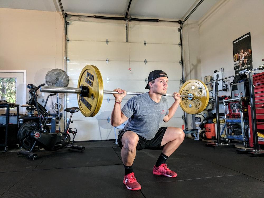 man lifting barbell on back inside gym