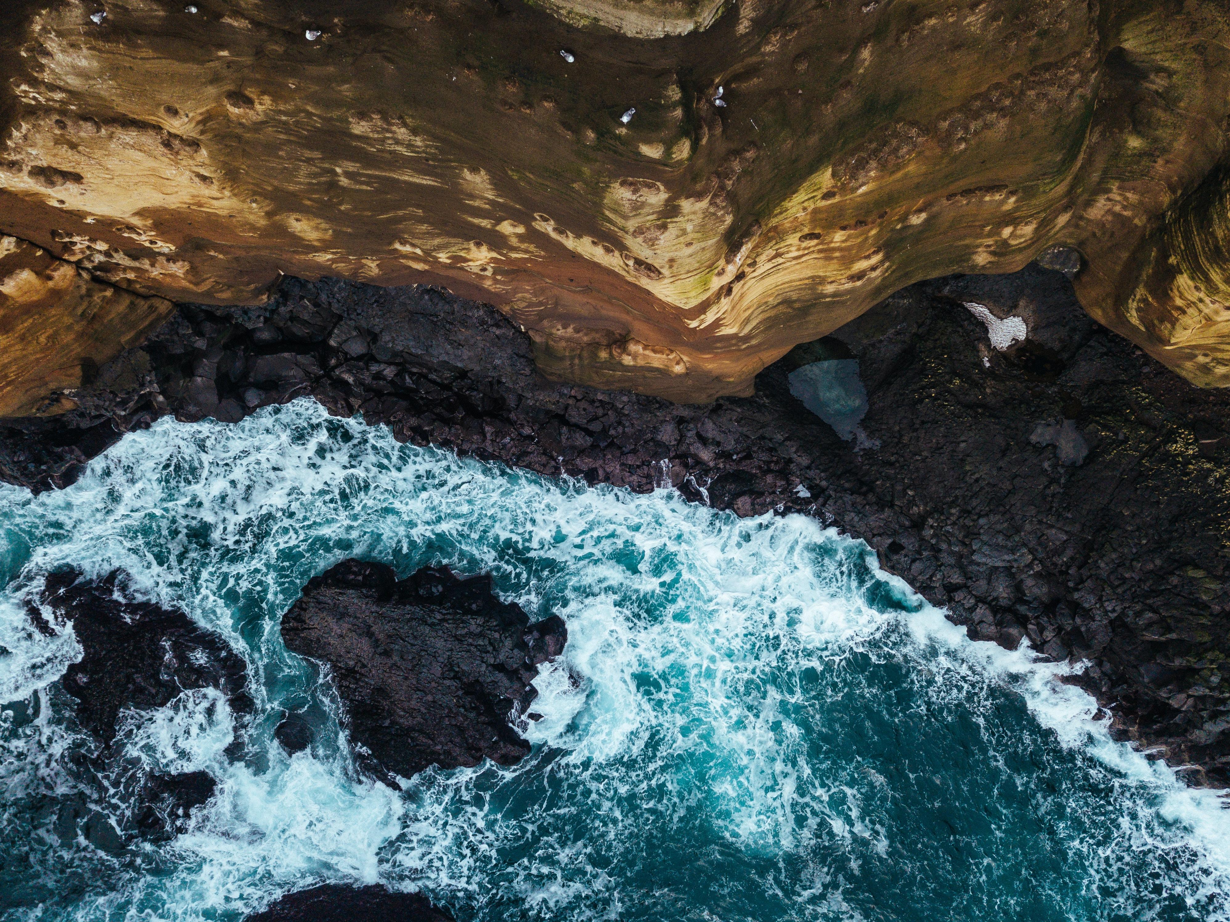 top-view photography of waves crashing on black rocks at daytime
