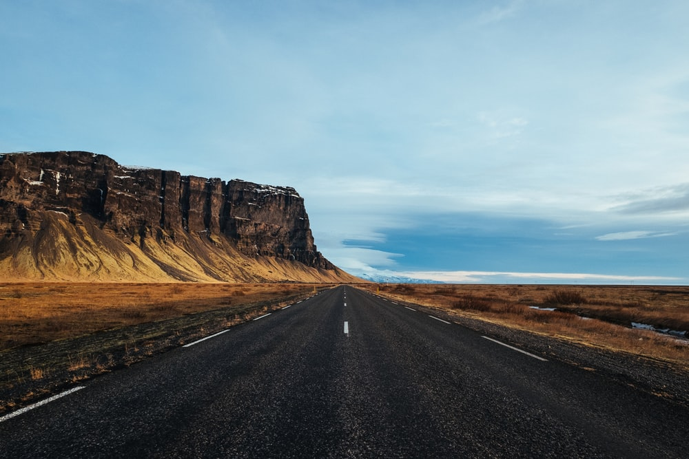 gray asphalt road in the middle of desert near black mountain during daytime