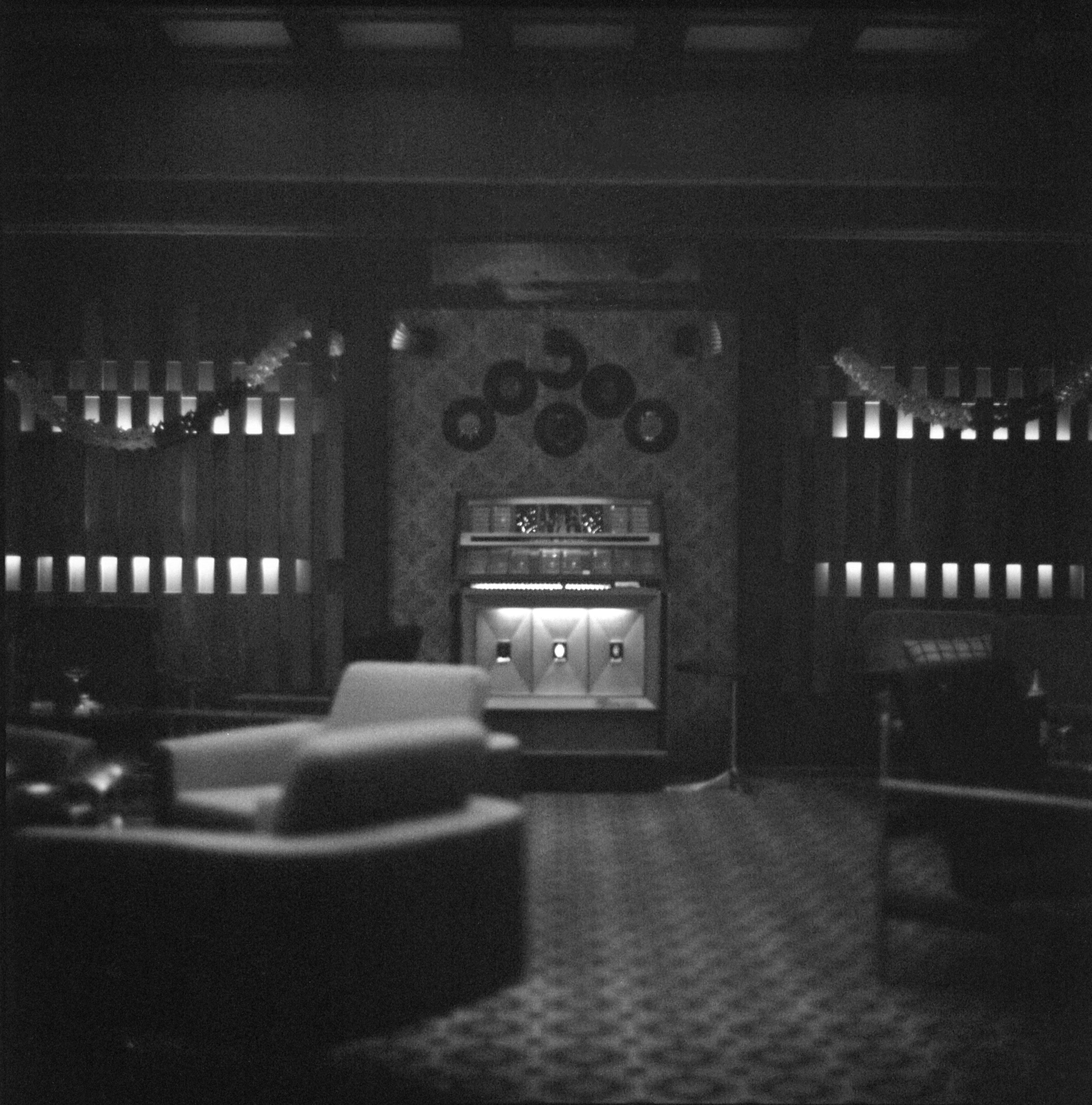 grayscale photo of chairs and fireplace