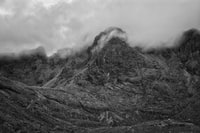 mountain range covered with clouds grayscale photography