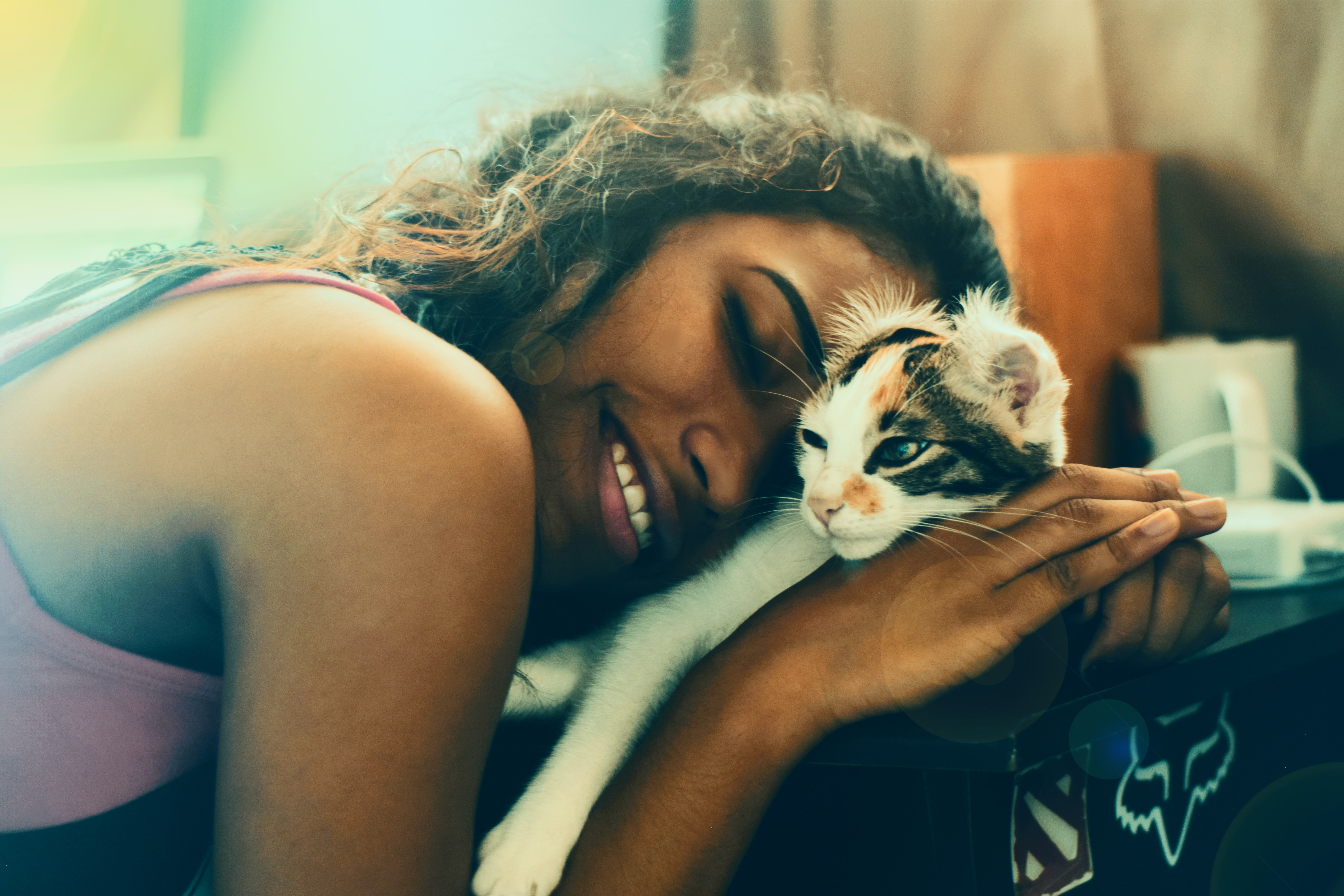 woman lying beside cat while smiling