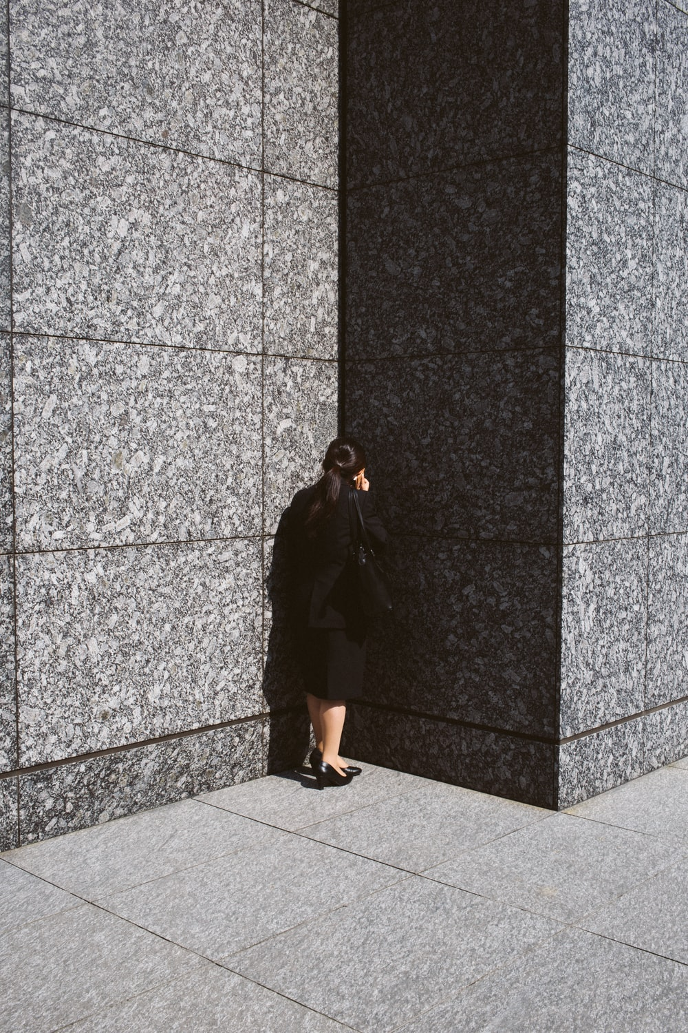 woman in black blazer and skirt holding smartphone