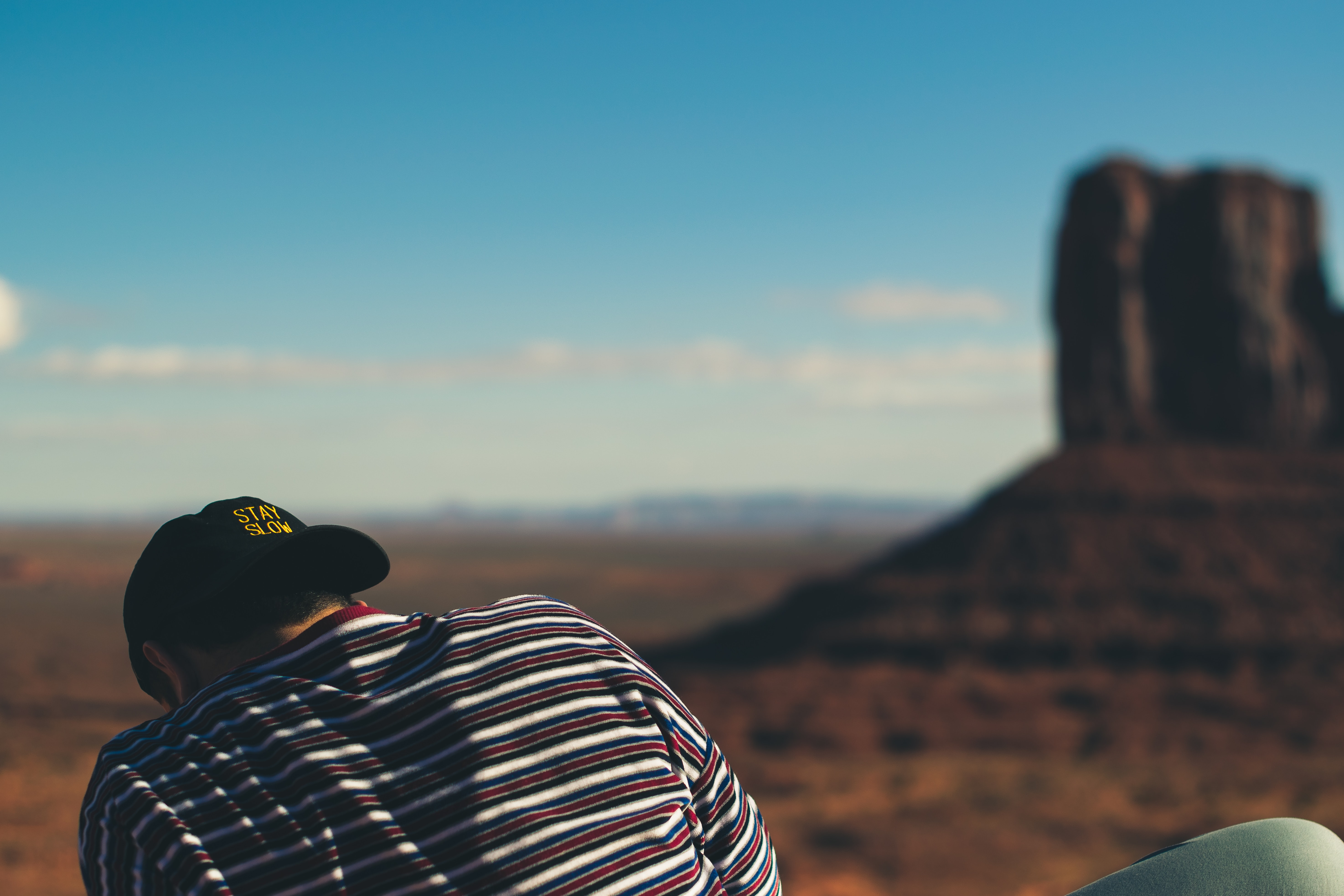 tilt-shift lens photography of person facing Monument Valley, Utah Arizona during daytime