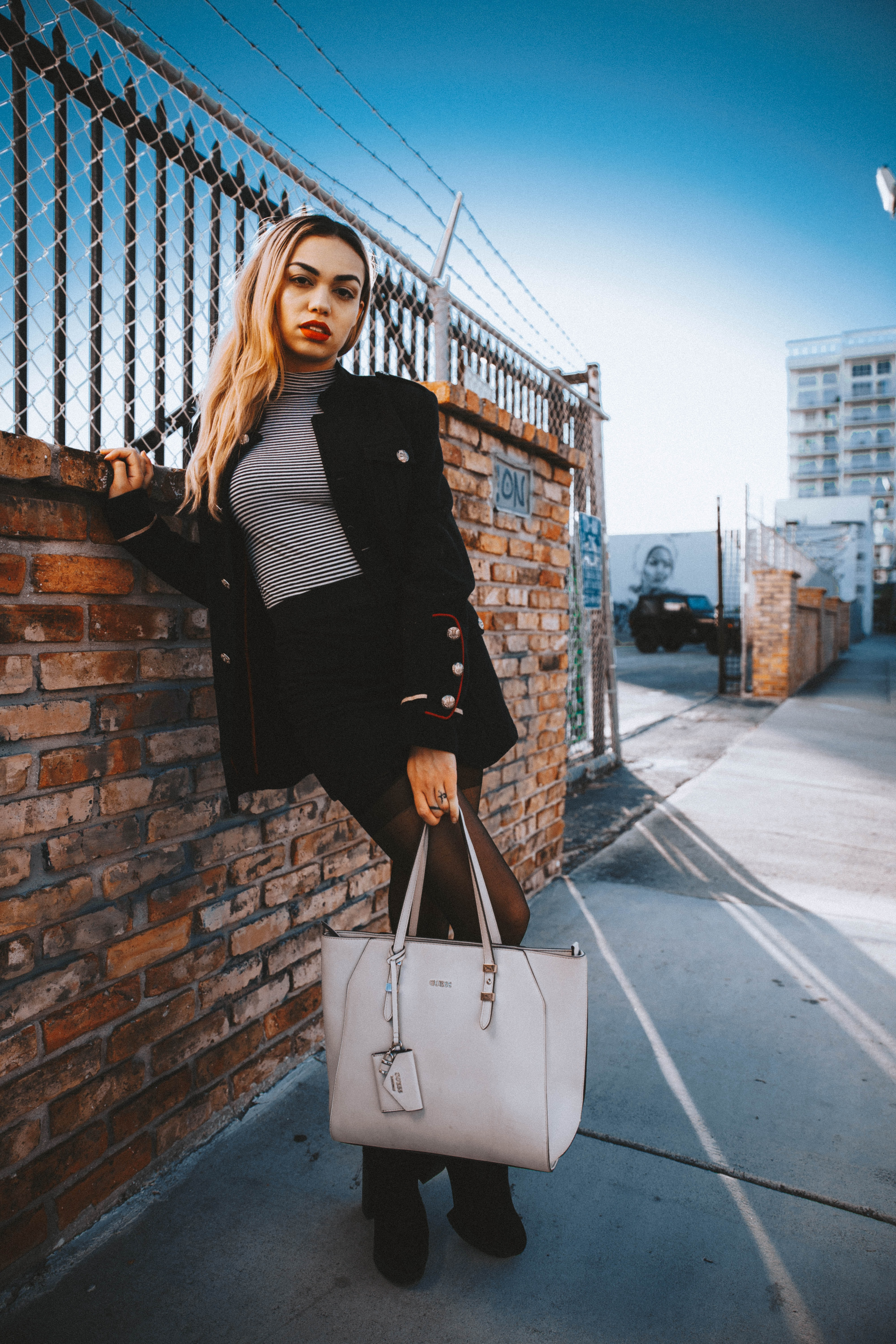 woman wearing black coat standing while holding tote bag besides concrete fence during daytime