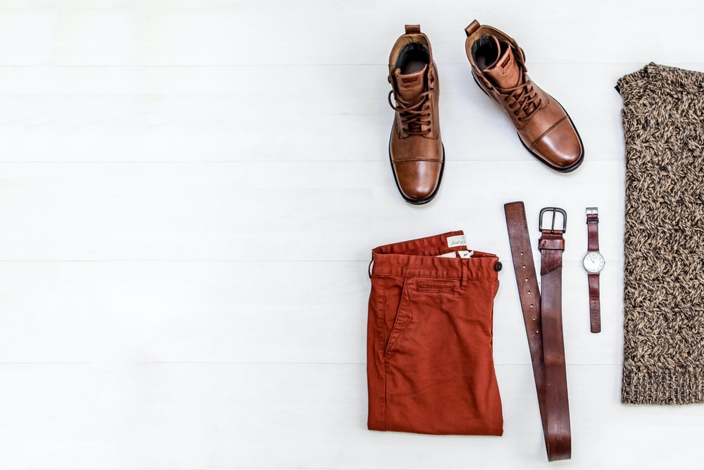 pair of brown leather boots, red shorts, brown leather belt, round gold-colored watch, and brown top